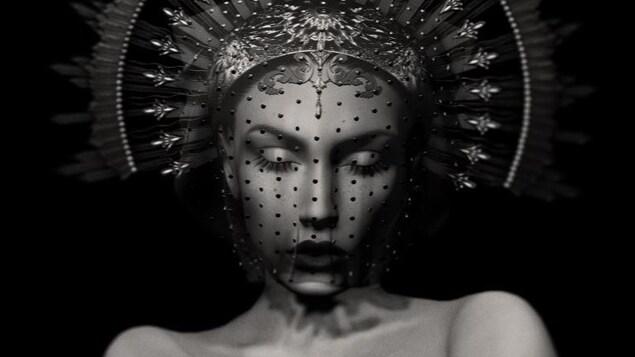 Détail de <i>Silence d'or</i>, photographie virtuelle en noir et blanc d'Anouk A., l'avatar 3D créé par Karoline Georges dans  Second Life. Le visage de la femme image est masqué par une voilette, et sa tête porte une auréole. Ses paupières sont fermées, ses épaules nues et elle a les bras croisés.