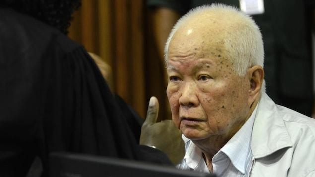 Un homme très âgé, au crâne dégarni, discute dans une salle de cour.