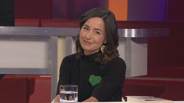 Elle porte un coeur vert sur son chandail.