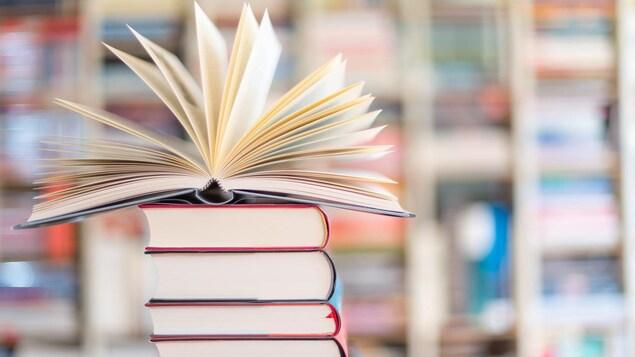Un livre ouvert sur une pile de livres fermés.