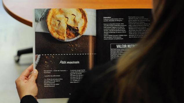 La nutritionniste en génétique Geneviève Lafrance tient son livre de recettes ouvert et regarde la recette du pâté mexicain.