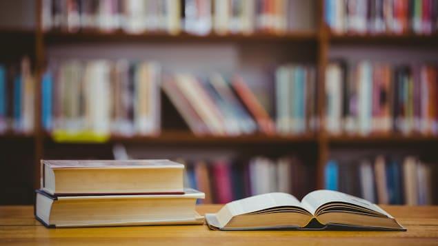 Deux livres fermés et un livre ouvert sur une table