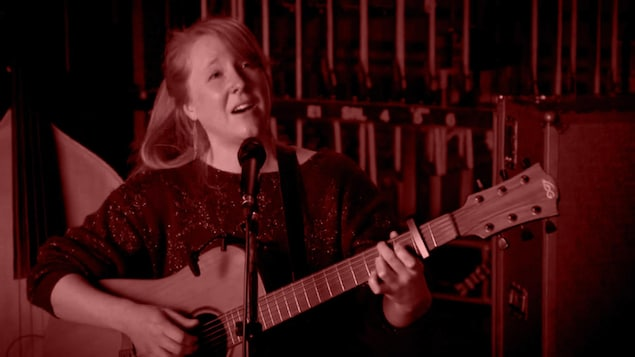 La chanteuse Lorène Charmetant chante en jouant de la guitare.