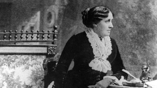 Portrait en noir et blanc, et de profil, de Louisa May Alcott, qui porte un chignon.