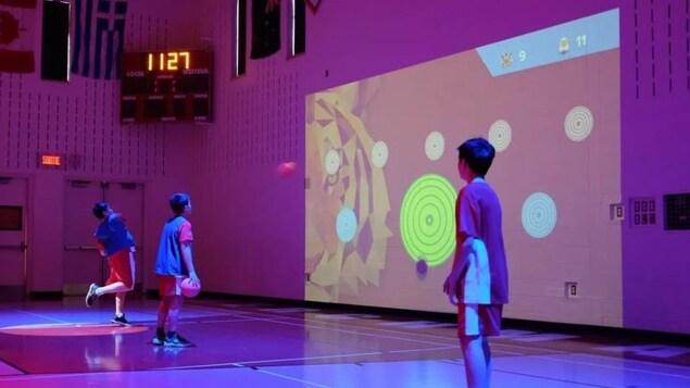 Des jeunes garçons lancent des ballons contre un écran interactif dans un gymnase.