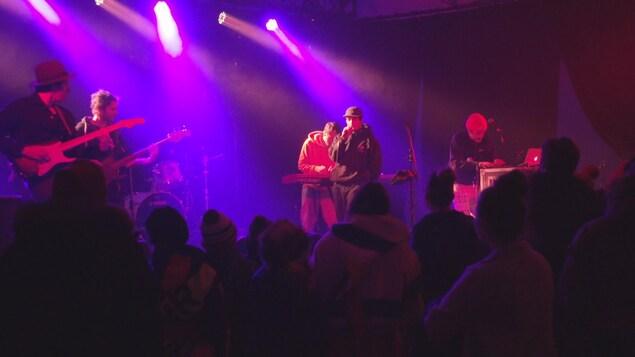 Un groupe de musique performe sous les projecteurs mauves d'une scène.
