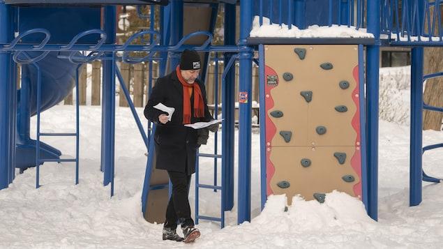 Luc Rabouin regarde des documents près d'une aire de jeux.