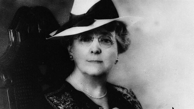 Assise sur une chaise, Lucy Maud Montgomery, portant un chapeau blanc et des lunettes, regarde l'objectif.