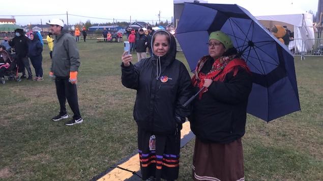 Une femme se photographie avec une autre femme qui porte un parapluie.