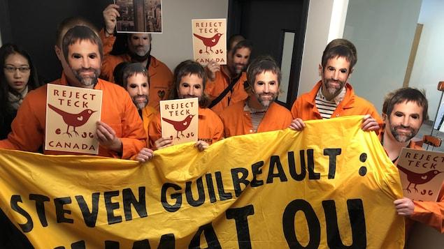Des manifestants portant un masque représentant le visage de Steven Guilbeault et une bannière lui demandant de choisir entre le climat et Teck Resources.