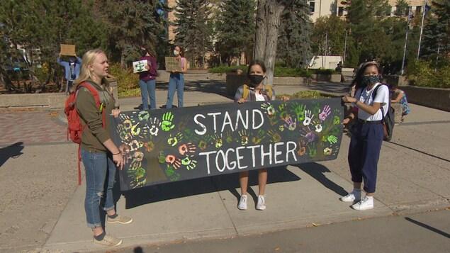 Trois manifestantes tiennent une pancarte où il est inscrit en anglais « stand together ».