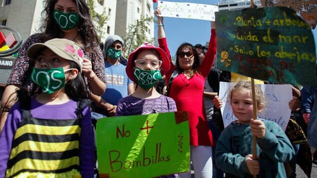 Des enfants, dont le plus jeune semble avoir environ 7 ans, manifestent entourés de leurs parents, en tenant des pancartes et en arborant un masque sur la bouche où il est écrit S.O.S.