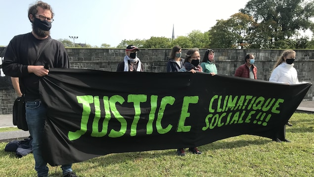 Des manifestants qui portent une banderole. Ils ont des masques au visage.