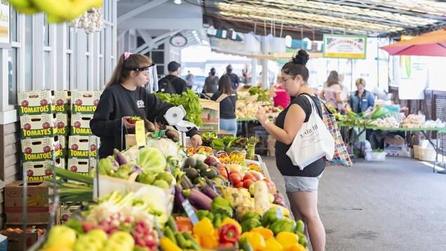 Dans un marché public, une femme fait ses achats devant un étal de légumes, servie par une employée.