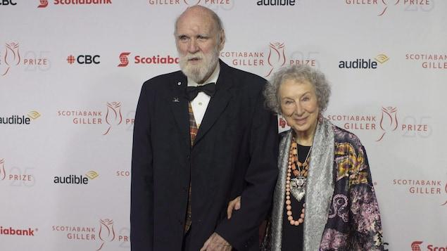 Margaret Atwood et Graeme Gibson sourient sur un tapis rouge.