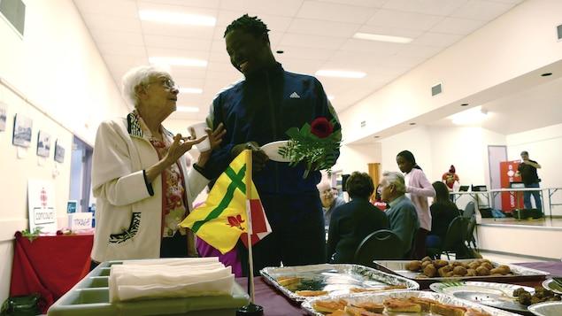 Une femme âgée et un jeune homme ont une discussion joyeuse devant un buffet. Derrière eux, des personnes sont attablées.