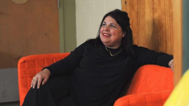 Maria Pullara assise sur un divan orange au centre de sa classe.