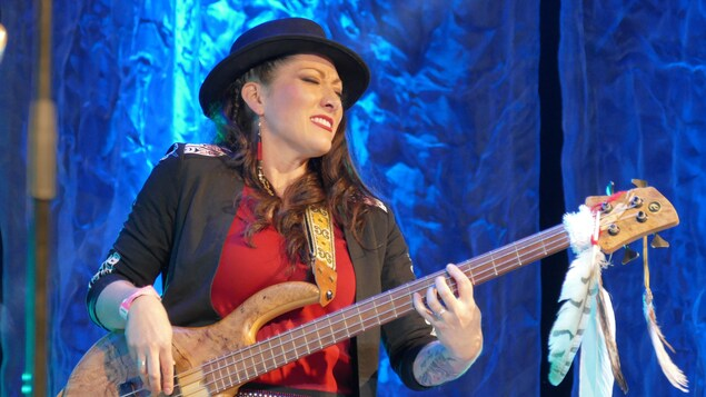Marie-Josée Dandeneau jouant de la basse sur scène.
