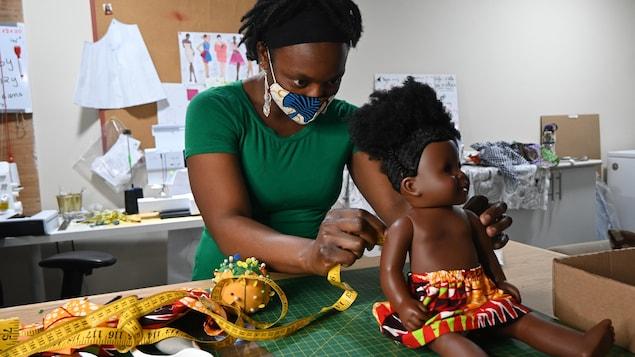 Marie Rosette Mikulu est en train de prendre les mesures d'une poupée afin de lui faire un habit.