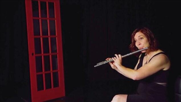 La musicienne Marie-Véronique Bourque joue de la flûte traversière dans un décor sombre contenant seulement une porte rouge.