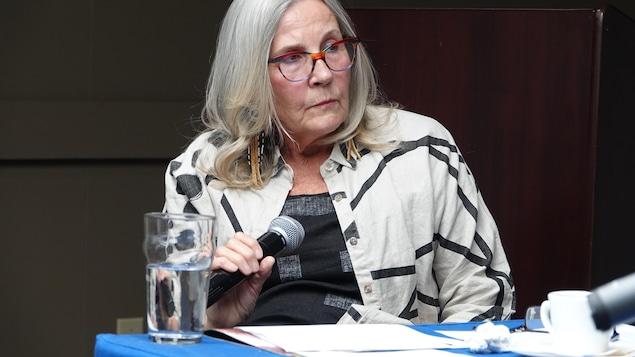 Marie Wilson est assise et tient un micro.