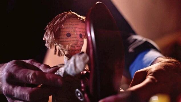 Une marionnette d'un jeune homme en papier mâché qui s'approche d'un soulier.