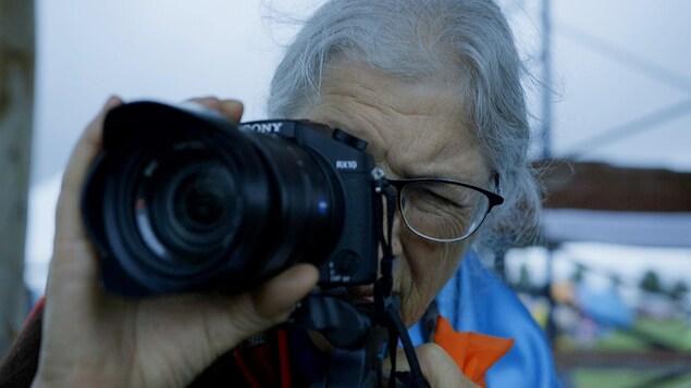 La cinéaste métisse Marjorie Beaucage regarde dans son appareil photo reflex.