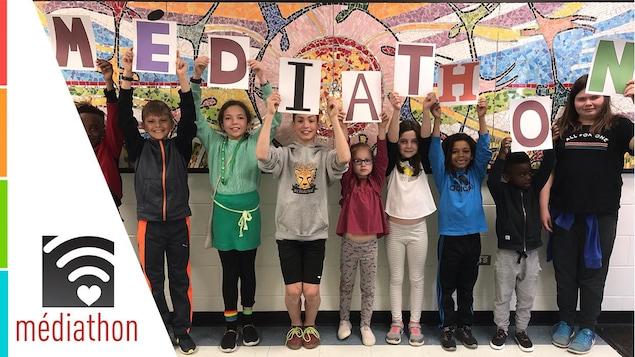 Des enfants tiennent des lettres pour former le mot « Médiathon ».
