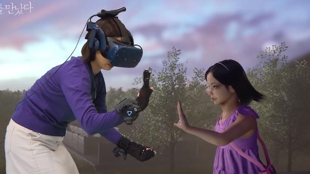 Un mère portant un casque de réalité virtuelle et des gants haptiques tend la main vers une version numérique de sa fille décédée.