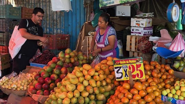 Rodolfo Castellanos devant des étals de fruits et légumes.