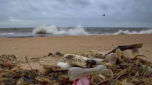 Des détritus en plastique sur une plage où la mer est agitée.