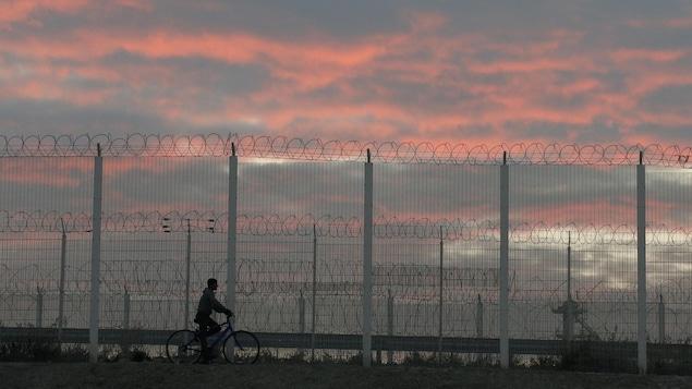 Un homme roule à bicyclette le long d'une clôture barbelée au coucher du soleil.