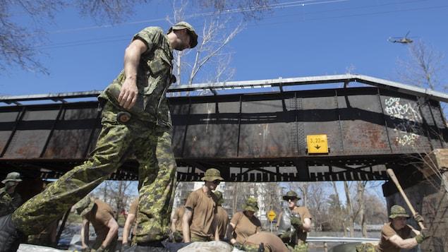Des soldats canadiens travaillent près d'un pont à Montréal.