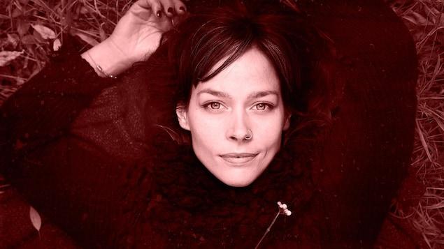 Portrait de la chanteuse Mireille Moquin couchée dans l'herbe.