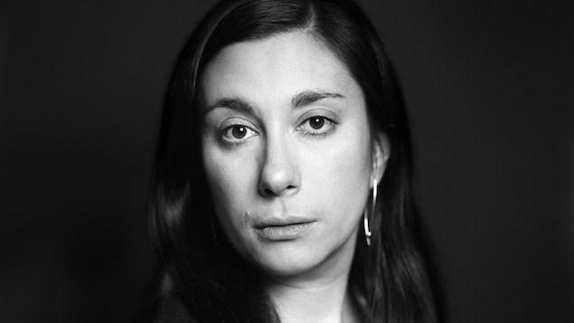 Sur cette photo en noir et blanc, une femme aux longs cheveux foncés et portant un haut noir sans manche regarde la caméra le visage tourné vers la droite.