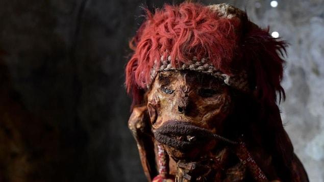 Photo d'une momie coiffée d'un accessoire rouge.