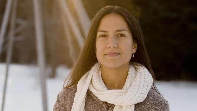 Une femme souriante pose à l'extérieure avec de la neige en arrière-plan.