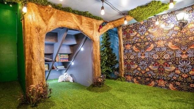 Le plancher de la pièce est recouvert de faux gazon et une bibliothèque est construite à l'intérieur d'un faux arbre.