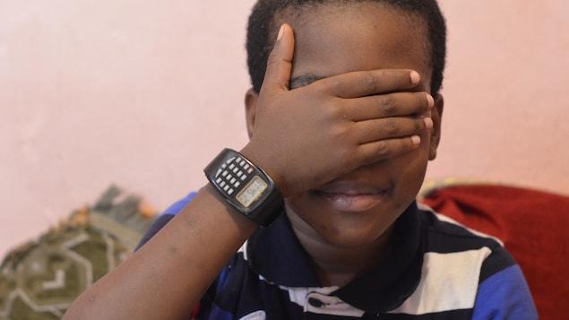 Un enfant met sa main devant ses yeux
