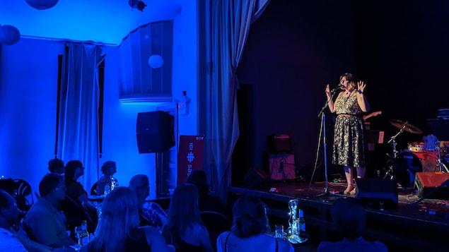 Dans une salle de spectacle, une artiste chante sur scène face à un public qui l'écoute attentivement.