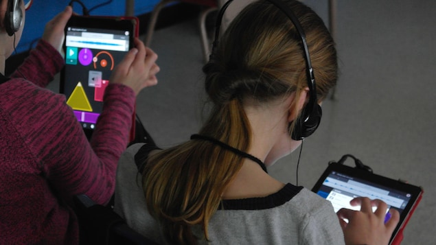 Des jeunes explorent une application sur une tablette.