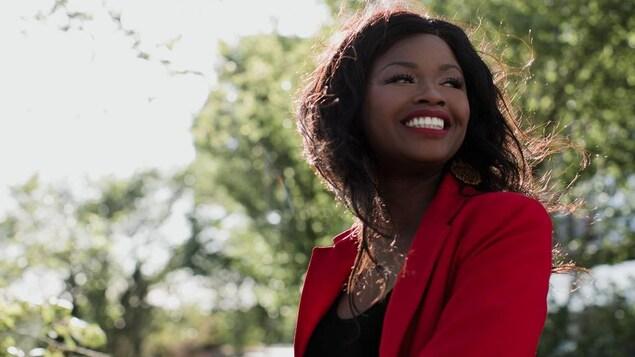 Une femme noire placée de trois-quart regarde au loin par-dessus son épaule, avec un grand sourire. Le soleil tombe sur sa chevelure lâchée au vent. Des arbres sont en arrière plan.