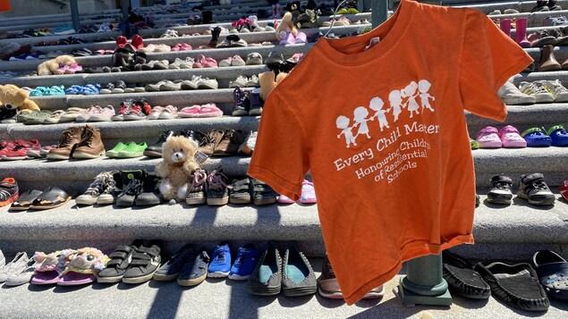 Un chandail orange devant 215 paires de souliers sur les marches du Palais législatif.