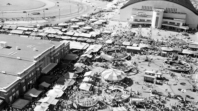 Tentes, manèges et foule dense durant une belle journée d'été, en pleine exposition sur la grande place du Colisée durant les années 1950.