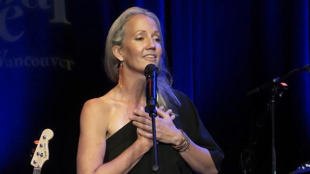 La musicienne Pascale Goodrich-Black derrière un micro, les mains croisées sur la poitrine.