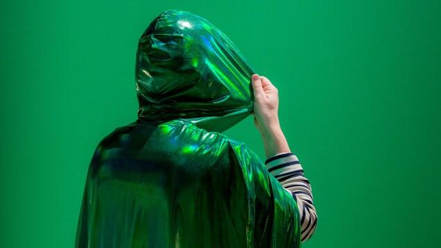 une personne de dos avec une capuche verte sur la tête.