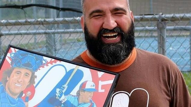 Portrait de l'auteur Patrick Beauséjour souriant devant un terrain de sport et tenant à la main un tableau représentant des joueurs de baseball des Expos.