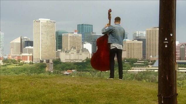 Paul Cournoyer debout avec son violoncelle sur le haut d'une falaise avec vue sur le centre-ville d'Edmonton.