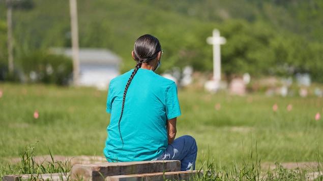 Un homme est assis dans un champ.