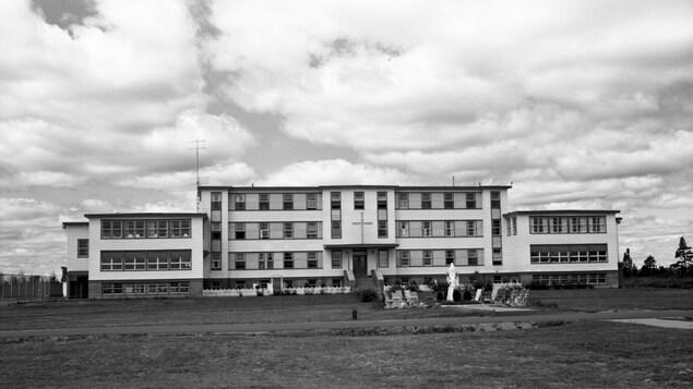 Une photo en noir et blanc du pensionnat, un bâtiment en forme de croix sur un grand terrain de gazon.